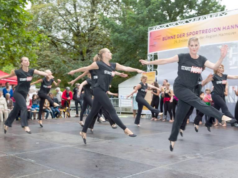 Frauen tragen schwarze Sportkleidung und tanzen auf einer Bühne.