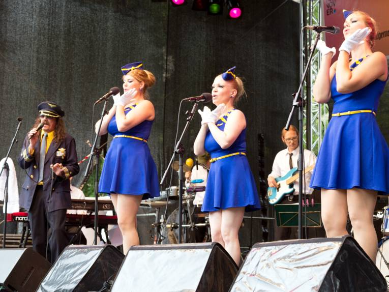 Drei Frauen tragen blaue Kleider, die an die Uniform einer Flugbegleiterin erinnern und singen in Mikrofone. Daneben steht ein Mann, der die Fantasieuniform eines Flugkapitäns trägt und ebenfalls in ein Mikrofon singt.