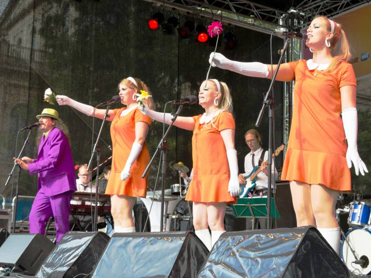Drei Frauen tragen orangefarbene Kleider und singen in Mikrofone. Daneben steht ein Mann, der ebenfalls in ein Mikrofon singt und einen violetten Anzug trägt.