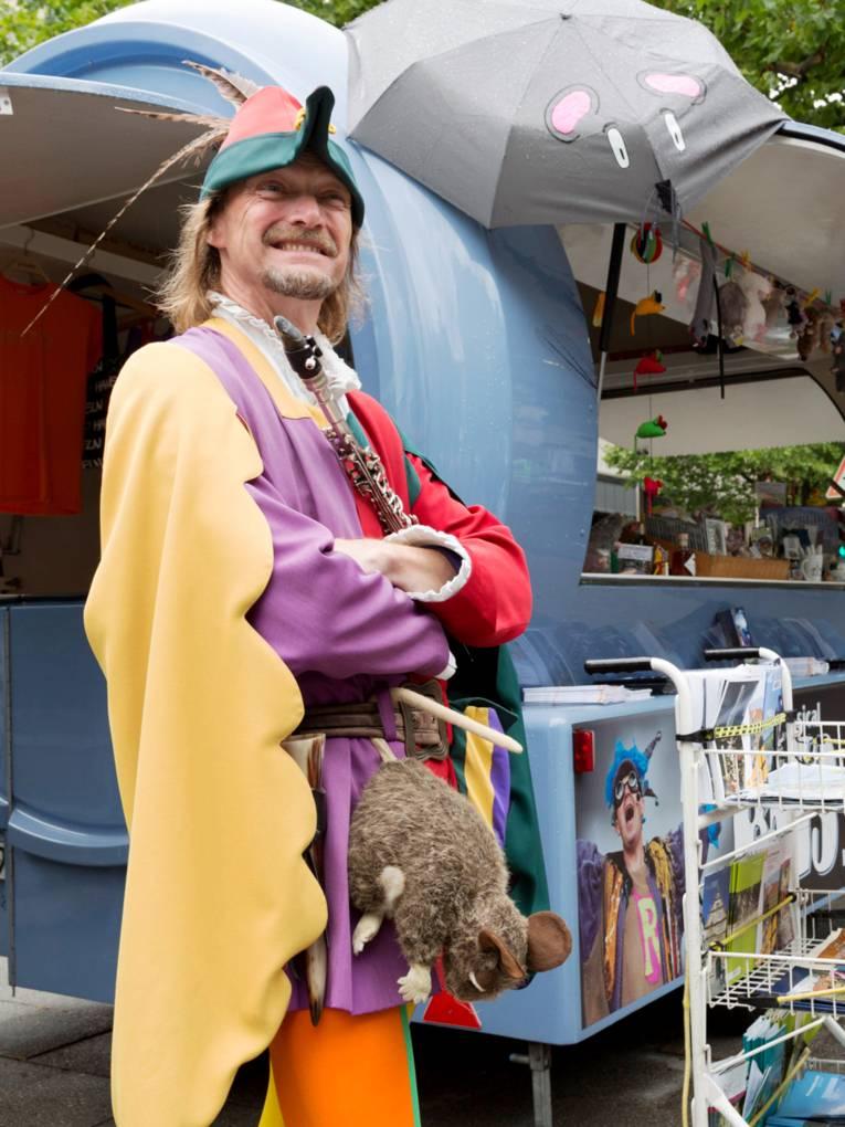 Ein Mann trägt ein buntes Kostüm, an seinem Gürtel baumelt eine Plüschratte und vor der Brust hält er eine Flöte. Hinter ihm ist ein Marktwagen mit Souvenirs der Stadt Hameln.