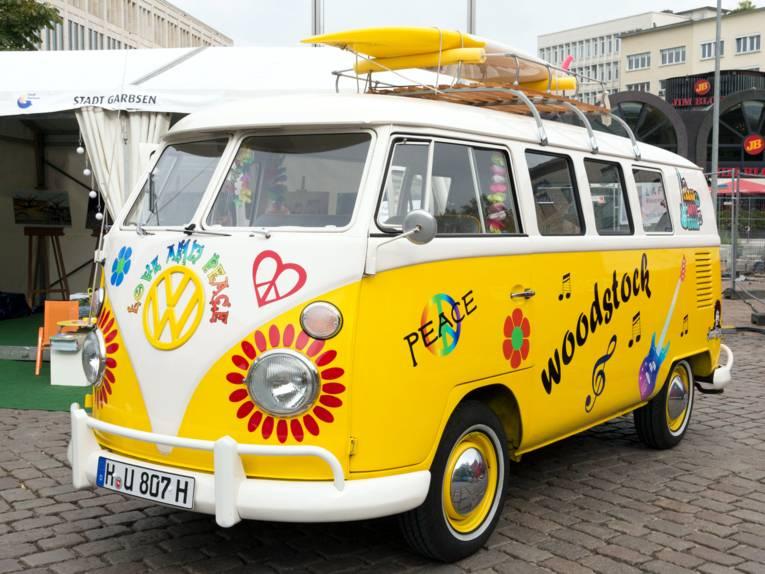 Ein VW Transporter t1 ist im Stil der Hippie-Bewegung lackiert und beschriftet. Blumen, das Friedenszeichen und weitere Symbole und Worte zieren den Lack.