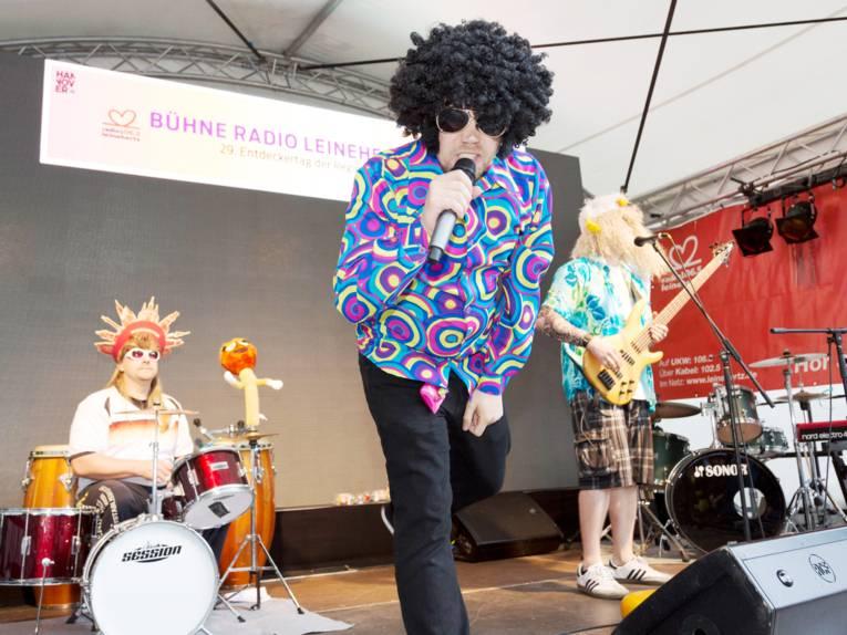 Ein Sänger, ein Gitarrist und ein Schlagzeuger spielen auf einer Bühne, sie tragen dabei besonders ausgefallene, bunte Kleidung und Perücken.