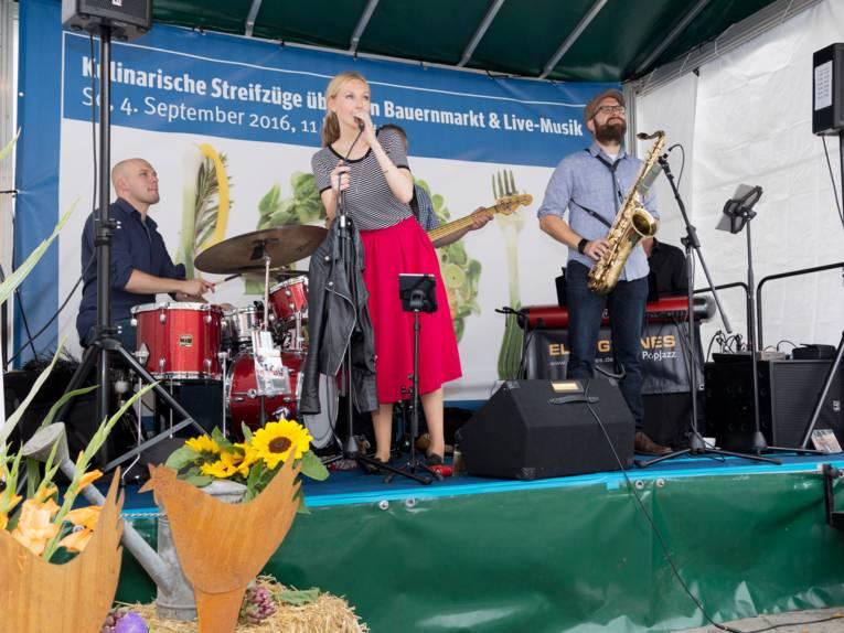 Drei Musiker und eine Sängerin spielen auf einer Bühne.