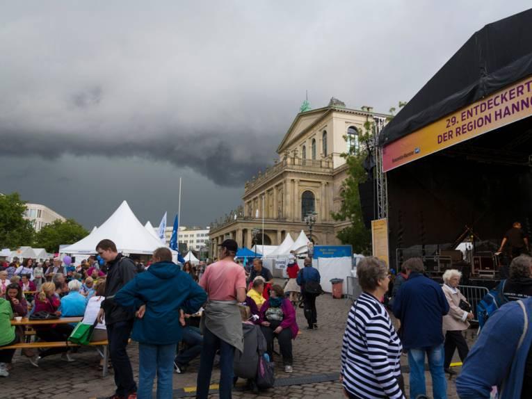 Eine große Bühne und Zelte sind auf dem Opernplatz in Hannover, im Hintergrund ist das Operngebäude. Am Himmel ziehen sich dunkle Wolken zusammen. Menschen gehen über den Platz, stehen oder sitzen an Festzeltgarnituren.