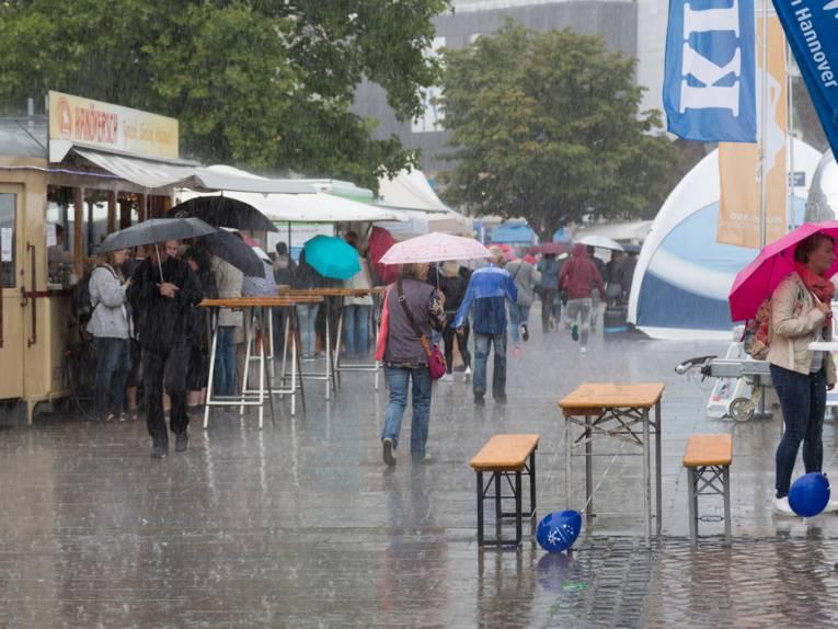 Auf dem Opernplatz in Hannover stehen Zelte und Infostände. Es regnet stark und es bilden sich Pfützen auf dem Pflaster. Menschen gehen unter aufgespannten Regenschirmen durch den Regen.