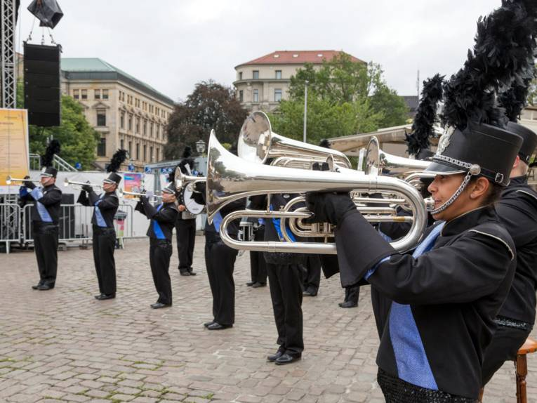 Musiker tragen eine Uniform in den Farben Blau und Schwarz und spielen auf Blechblasinstrumenten.