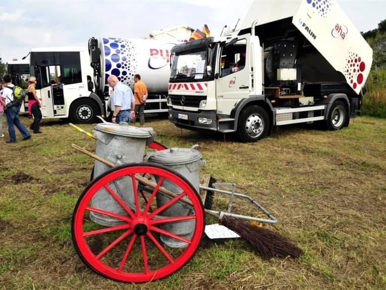Auf einem Handwagen mit großen Speichenrädern stehen zwei verzinkte Mülltonnen, zwei Besen sind am Fahrgestell befestigt. Im Hintergrund sind moderne Müllfahrzeuge und eine Kehrmaschine.