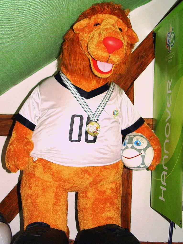 Unter einer Dachschräge steht eine 230 Zentimeter große Puppe in Form eines aufrecht stehenden Löwen. Der Löwe trägt ein weißes Fußballtrikot und schwarze Fußballschuhe, außerdem hat er eine Medaille um den Hals und in der linken Pfote einen Fußball mit Gesicht.