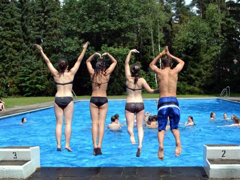 Drei Mädchen und ein Junge springen in ein Schwimmbecken. Im klaren Wasser sind weitere Schwimmerinnen und Schwimmer.