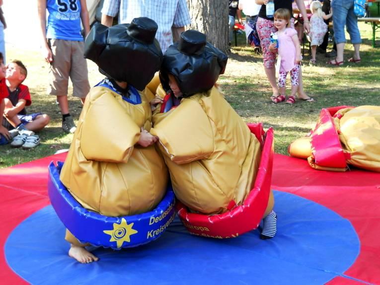 Zwei Kinder stecken in gut gepolsterten Spezialanzügen und ringen miteinander im Stil asiatischer Sumoringer.